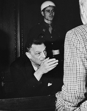 Defendant Arthur Seyss-Inquart talks to fellow defendant Wilhelm Frick during a court recess.