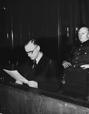 Defendant Alfred Rosenberg, the former Chief Nazi Party ideologist, reads a document during the International Military Tribunal trial of war criminals at Nuremberg. Behind him is his co-defendant General Alfred Jodl, formerly the Chief of Staff for the Army. Nuremberg, Germany, 1945–1946.