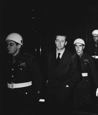 Defendant Hans Fritzsche enters the Nuremberg courtroom under American guard.