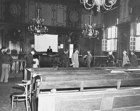 The courtroom in the Palace of Justice, chosen as the location for the International Military Tribunal trial of war criminals. This photograph shows the courtroom before any repairs or alterations were made. Nuremberg, Germany, August-September 1945.