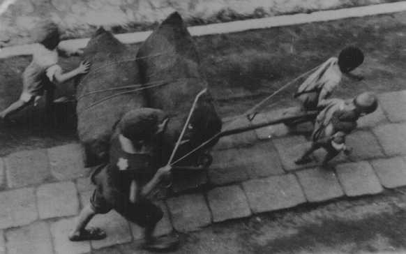Jewish children forced to haul a wagon. Lodz ghetto, Poland, wartime.
