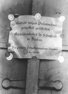 """Un avis dit """"Commerce fermé par la police pour cause de profits illicites. Le propriétaire est en détention préventive à Dachau."""" Signé par le chef de la police Heinrich Himmler. Munich, Allemagne, avril ou mai 1933."""