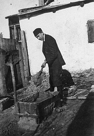 Naftali Saleschutz prepares cement for the foundation of a sukkah (a hut-like structure used to celebrate the Jewish holiday of Sukkot). Kolbuszowa, Poland, 1937.