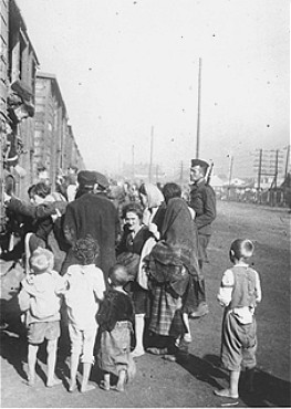 Under guard, Jewish men, women, and children board trains during deportation from Siedlce to the Treblinka killing center. Siedlce, Poland, August 1942.