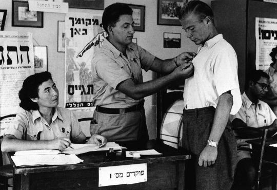 In the British army recruitment office in Tel Aviv, an official pins the symbol of the volunteer Jewish Brigade onto the shirt of a new recruit. Tel Aviv, Palestine, 1940-1941.