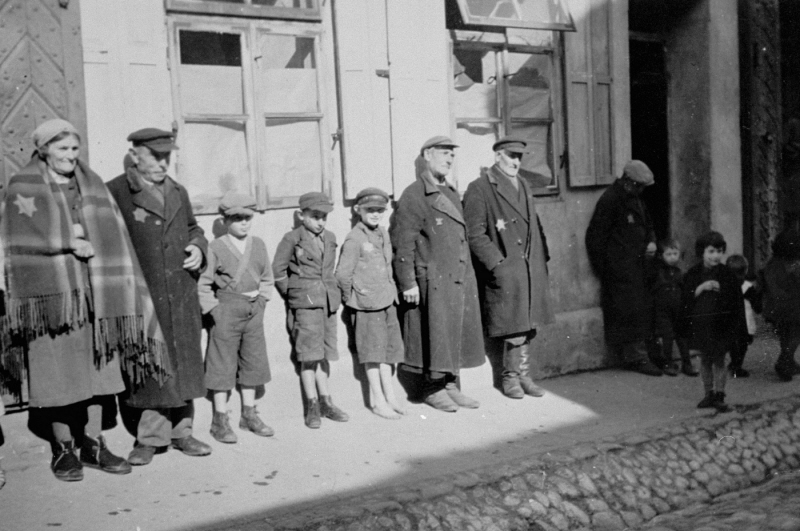 German Jewish adults and children wearing compulsory Jewish badges are lined up against a building. Weser, Germany, between 1941 and 1943.