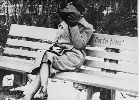 """Женщина, прикрывающая лицо рукой, сидит на парковой скамейке с надписью """"Только для евреев"""". Австрия, прибл. март 1938 года."""
