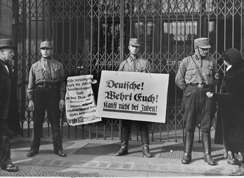 """اسٹارم ٹروپر(ایس اے) اراکین بائیکٹ کے نشانات اٹھائے ہوئے ایک یہودی دکان کا راستہ روکے کھڑے ہیں۔ ان نشانات میں سے ایک پر لکھا ہوا ہے: """"جرمنوں! اپنا دفاع کرو! یہودیوں سے خریدوفروخت مت کرو"""" برلن ، جرمنی، یکم اپریل، 1933"""