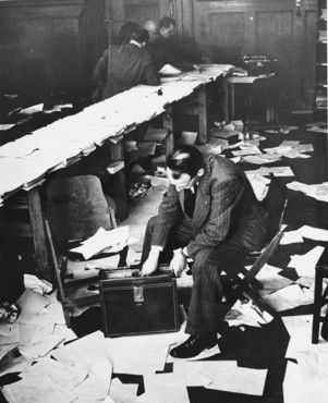 Gordon Dean, the public relations counsel to US Chief Prosecutor Robert Jackson, sorts papers in the press workroom at the end of a day at the International Military Tribunal.  December 11, 1945.