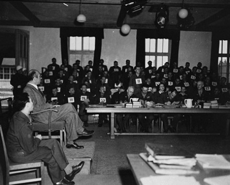 A witness testifies during the Mauthausen concentration camp trail. The man standing in the background is defendant Willy Eckert, a member of the SS.
