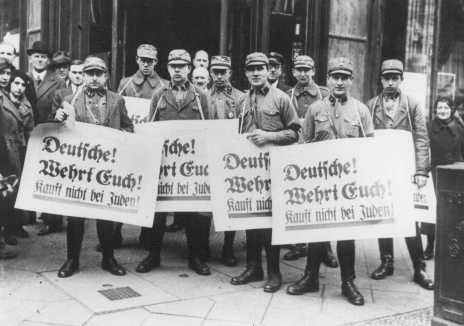 "During the anti-Jewish boycott, SA men carry banners which read ""Germans! Defend Yourselves! Do Not Buy From Jews!"" Berlin, Germany, March or April 1933."