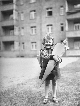 Berta Rosenheim poses with a large cone, traditionally filled with sweets and stationery, on her first day of school. Leipzig, Germany, April 1929.