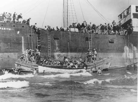 "Aliyah Bet (""illegal"" immigration) ship ""Parita,"" carrying 850 Jewish refugees, lands on a sandbank off the Tel Aviv coast. The British arrested the passengers and interned them at Atlit detention camp. Palestine, August 21, 1939."
