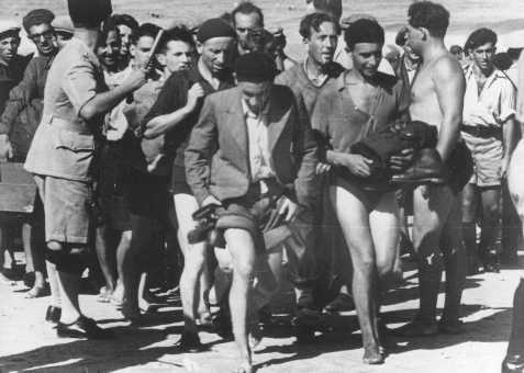 "A British policeman (left) organizes the arrest of passengers from the Aliyah Bet (""illegal"" immigration) ship ""Parita"" after they disembarked near Tel Aviv. Palestine, August 22, 1939."