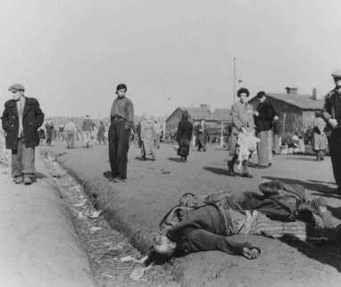Soon after liberation, camp survivors walk amidst dead bodies. Bergen-Belsen, Germany, after April 15, 1945.