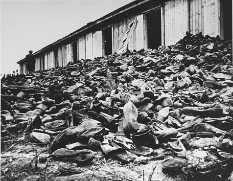 A Soviet soldier walks through a mound of victims' shoes piled outside a warehouse in Majdanek soon after the liberation. Majdanek, Poland, August 1944.