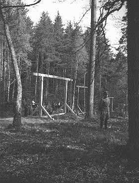 SS officers supervise the erection of a gallows, for the hanging of inmates, in a wooded areas by the Buchenwald concentration camp. Buchenwald, Germany, 1938-1940.