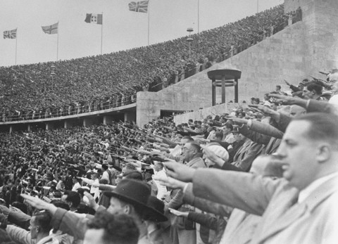In the Olympic Stadium, German spectators salute Adolf Hitler during the Games of the 11th Olympiad. Berlin, Germany, August 1936.