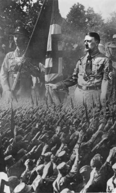 Picture postcard showing a crowd of saluting Germans superimposed on an enlarged image of Hitler and a Nazi stormtrooper. Munich, Germany, ca. 1932.