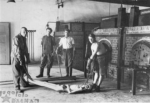 Survivors of the Dachau concentration camp demonstrate the operation of the crematorium by preparing a corpse to be placed into one of the ovens. Dachau, Germany, April 29-May 10, 1945.
