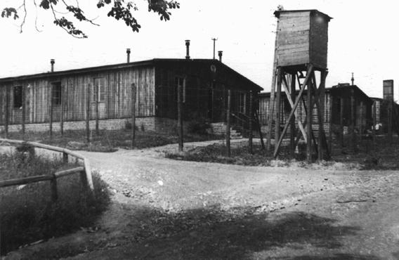 A watchtower and barracks at the Ohrdruf subcamp of the Buchenwald concentration camp. This photograph was taken after US forces liberated the camp. Ohrdruf, Germany, June 1945.