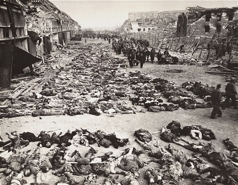 German civilians remove the bodies of prisoners killed in the Nordhausen concentration camp and lay them out in long rows outside the central barracks (Boelke Kaserne). Nordhausen, Germany, April 12, 1945.