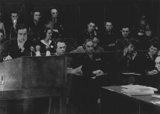 James McHaney, the American prosecutor, stands at the podium during the Pohl case as General Lucius Clay, US military governor, observes the proceedings. Nuremberg, Germany, January 13–November 3, 1947.
