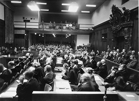 View of the courtroom as seen from the interpreters' section during the I. G. Farben Trial. The defense lawyers are in the foreground, the defendants are in the dock to the right, and the spectators' gallery is on the far side of the courtroom.