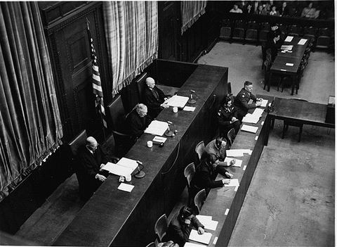 Members of the tribunal listen to the proceedings of the High Command Case. Seated from left to right on the judges' bench are Winfield B. Hale, Presiding Justice John C. Young, and Justin W. Harding.