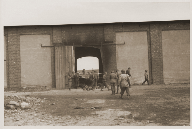 American troops inspect the site of the Gardelegen atrocity. In the background, German civilians exhume corpses who were buried in a mass grave by the SS. Germany, April 18, 1945.