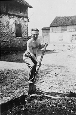 A Jewish man deported from Vienna, Austria, performs forced labor in the Opole Lubelskie ghetto. Poland, date uncertain.
