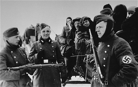 Young German soldiers assist in the deportation of Jews from the Zychlin ghetto to the Chelmno camp. The Nazis planned this deportation to fall on the Jewish holiday of Purim. Poland, March 3, 1942.