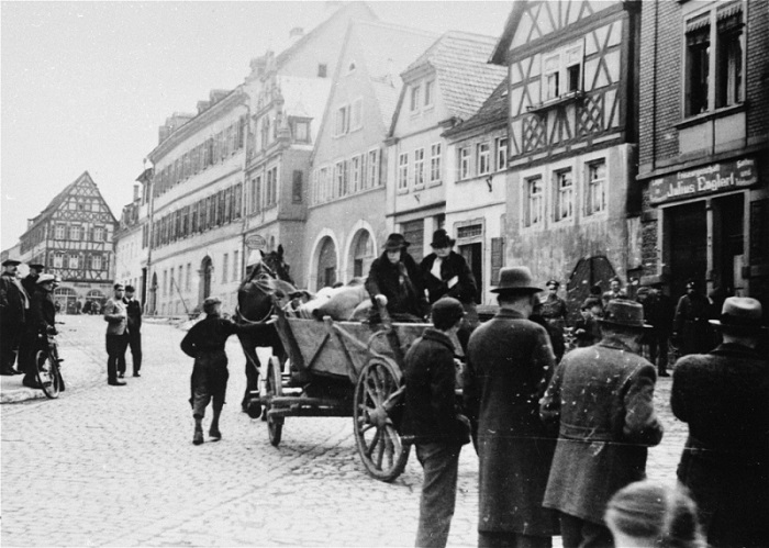 Two elderly Jewish women arrive at the Fränkischen Hof assembly center in a horse-drawn wagon during a deportation action in Kitzingen. Local residents watch. What responsibility does the man driving the wagon bear? Kitzingen, Germany, March 24, 1942.