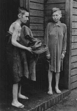 Two survivors in front of the women's barracks in the Bergen-Belsen concentration camp. Bergen-Belsen, Germany, April 1945.