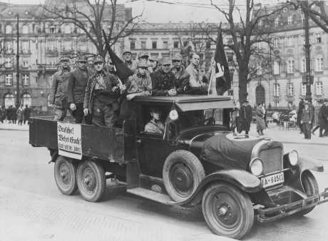 "Sign on truck carrying Storm Troopers (SA) urges ""Germans! Defend yourselves. Don't buy from Jews."" Berlin, Germany, April 1, 1933."