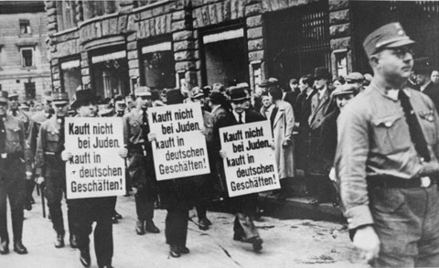 "Three Jewish businessmen are forced to march down a crowded Leipzig street while carrying signs reading: ""Don't buy from Jews. Shop in German businesses!"" Leipzig, Germany, 1935."