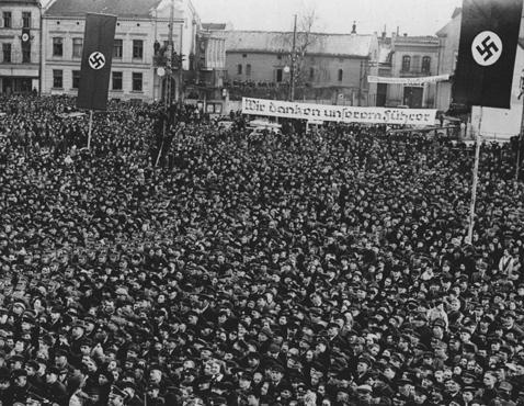 """A la suite de l'annexion allemande de Memel en Lituanie, une foule d'Allemands sur la place du marché de Memel écoutent Hitler parler. La banderole déclare : """"Nous remercions notre Führer."""" Memel (aujourd'hui Klaipeda), mars 1939."""