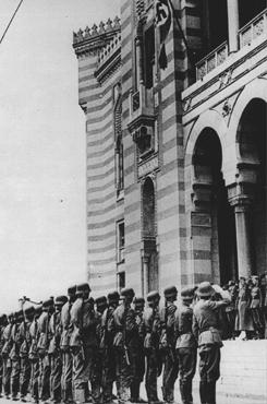 A flag bearing a swastika is raised over the city hall in Sarajevo after German forces captured the city. Sarajevo, Yugoslavia, April 16, 1941.