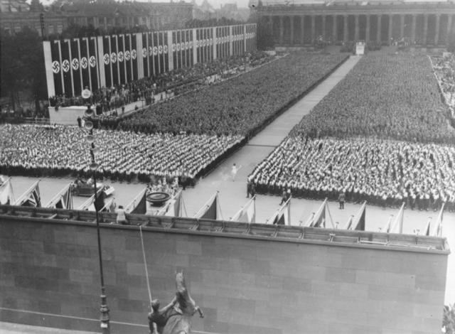 1936年8月1日に、ドイツのベルリンでヒトラーは第11回オリンピックを開会した。新しいオリンピックの儀式にのっとり、古代にオリンピックが開催されたギリシャのオリンピアからリレーで運ばれてきた聖火を掲げてランナーが到着した。この写真は、聖火を掲げてベルリン市内に入り、聖火台に向かう聖火リレーの最後のランナーを迎えて、第11回夏季オリンピックが開幕されようとするところ。1936年8月1日、ドイツ、ベルリン。