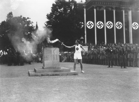 The last of the 3,000 runners who carried the Olympic torch from Greece lights the Olympic Flame in Berlin to start the 11th Summer Olympic Games. Berlin, Germany, August 1936.