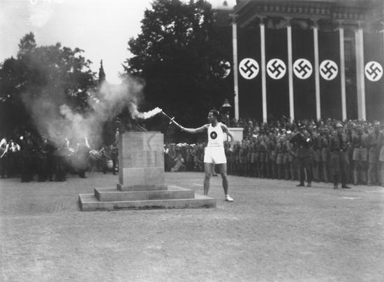 Последний из 3000 бегунов, пронесших олимпийский факел из Греции, зажигает Олимпийский огонь в Берлине, символизируя начало XI летних Олимпийских игр. Берлин, Германия, август 1936 г.