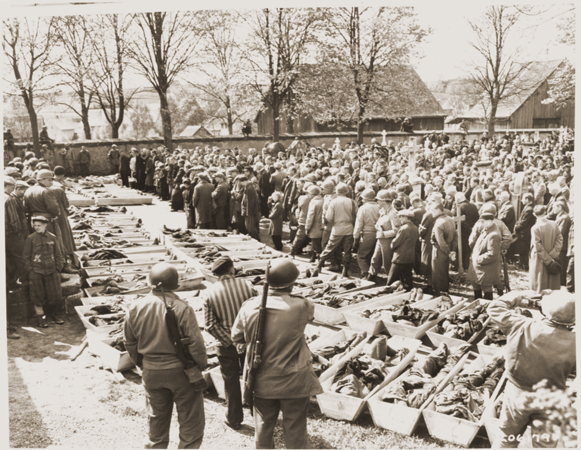 US troops and German civilians from Neunburg vorm Wald attend a funeral service for Polish, Hungarian, and Russian Jews found in the forest near their town. The victims were shot by the SS while on a death march from Flossenbürg. Neunburg, Germany, April  29, 1945.