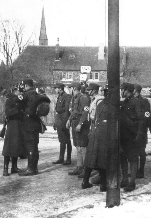 German police [Schutzpolizei] who are posted at the Berlin city line search SA men for weapons before allowing them to proceed to a rally in the capital. Berlin, Germany, 1927.