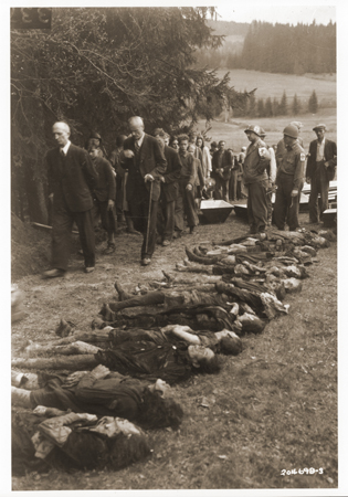 Under the supervision of American medics, German civilians file past the bodies of Jewish women exhumed from a mass grave in Volary. The victims died at the end of a death march from Helmbrechts, a subcamp of Flossenbürg. Volary, Czechoslovakia, May 11, 1945.