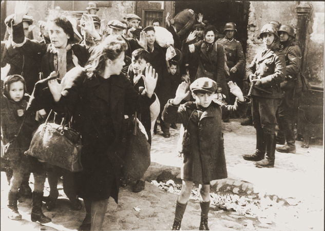 Jews captured by German troops during the Warsaw Ghetto uprising in April-May 1943.  This photograph appeared in the Stroop Report, an album compiled by SS Major General Juergen Stroop, commander of German forces that suppressed the Warsaw ghetto uprising.  The album was introduced as evidence at the International Military Tribunal at Nuremberg.  In the decades since the trial this photo has become one of the iconographic images of the Holocaust.