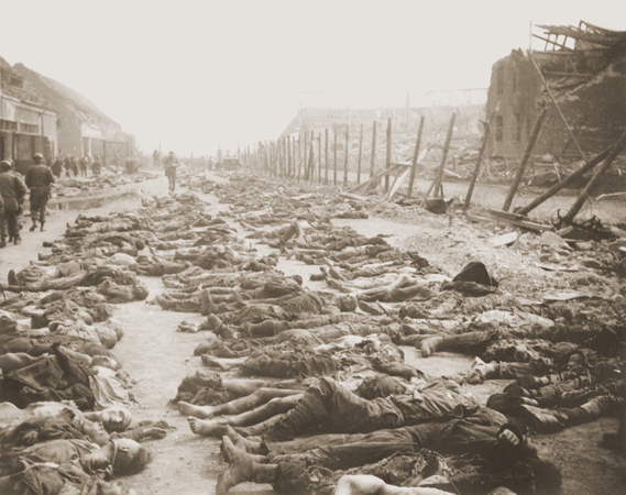 View of the main street of the Nordhausen concentration camp, outside of the central barracks (Boelke Kaserne), where the bodies of prisoners have been laid out in long rows. Nordhausen, Germany, April 13-14, 1945.