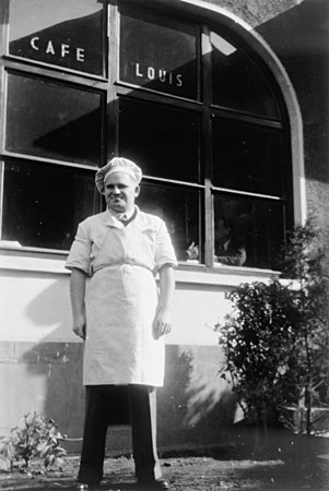 El refugiado judío-alemán Erwin Eisfelder fuera del Café Louis en la calle Ward. El café llevaba ese nombre en honor de su padre y era un lugar de reunión popular entre los refugiados en Shanghai durante los años de la guerra. Shanghai, China, hacia 1944.