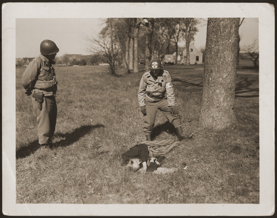 An American medic and soldier stand by the corpse of a prisoner shot on the road near Gardelegen. The prisoner was shot by the SS when he was too exhausted to continue on a death march. Germany, April 14-18, 1945.