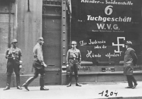 """Reparti d'assalto nazisti montano la guardia all'esterno di un negozio di proprietà di Ebrei, in Austria, poco dopo l'annessione del paese da parte della Germania. La scritta sui vetri recita: """"Porco Ebreo, che le tue mani possano marcire e cadere!"""" Vienna, Austria, marzo 1938."""