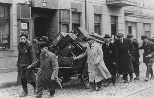 Jews deported from Prague, Czechoslovakia, move their belongings through the streets. Lodz ghetto, Poland, November 20, 1941.